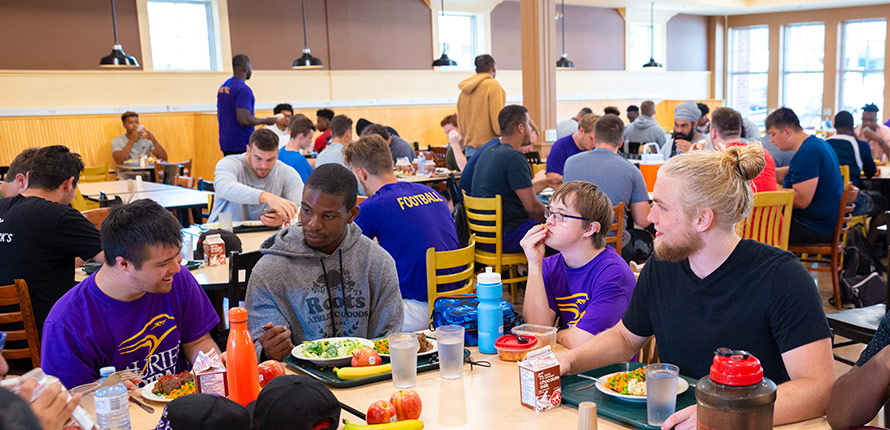Laurier football players eating lunch with Light House members.