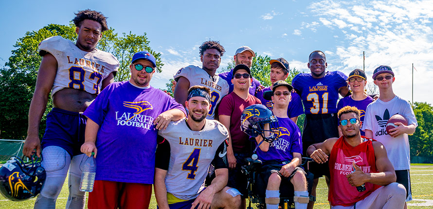 Coach Faulds and Laurier football players stand with LIght House members for a picture.