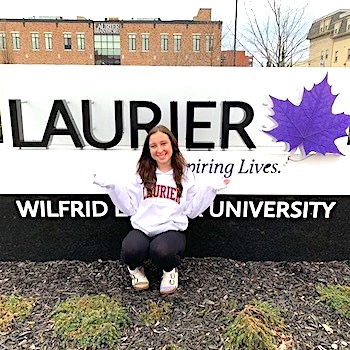 Madeline Campbell in front of Laurier sign
