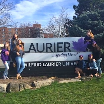 Students Standing Around Laurier Sign